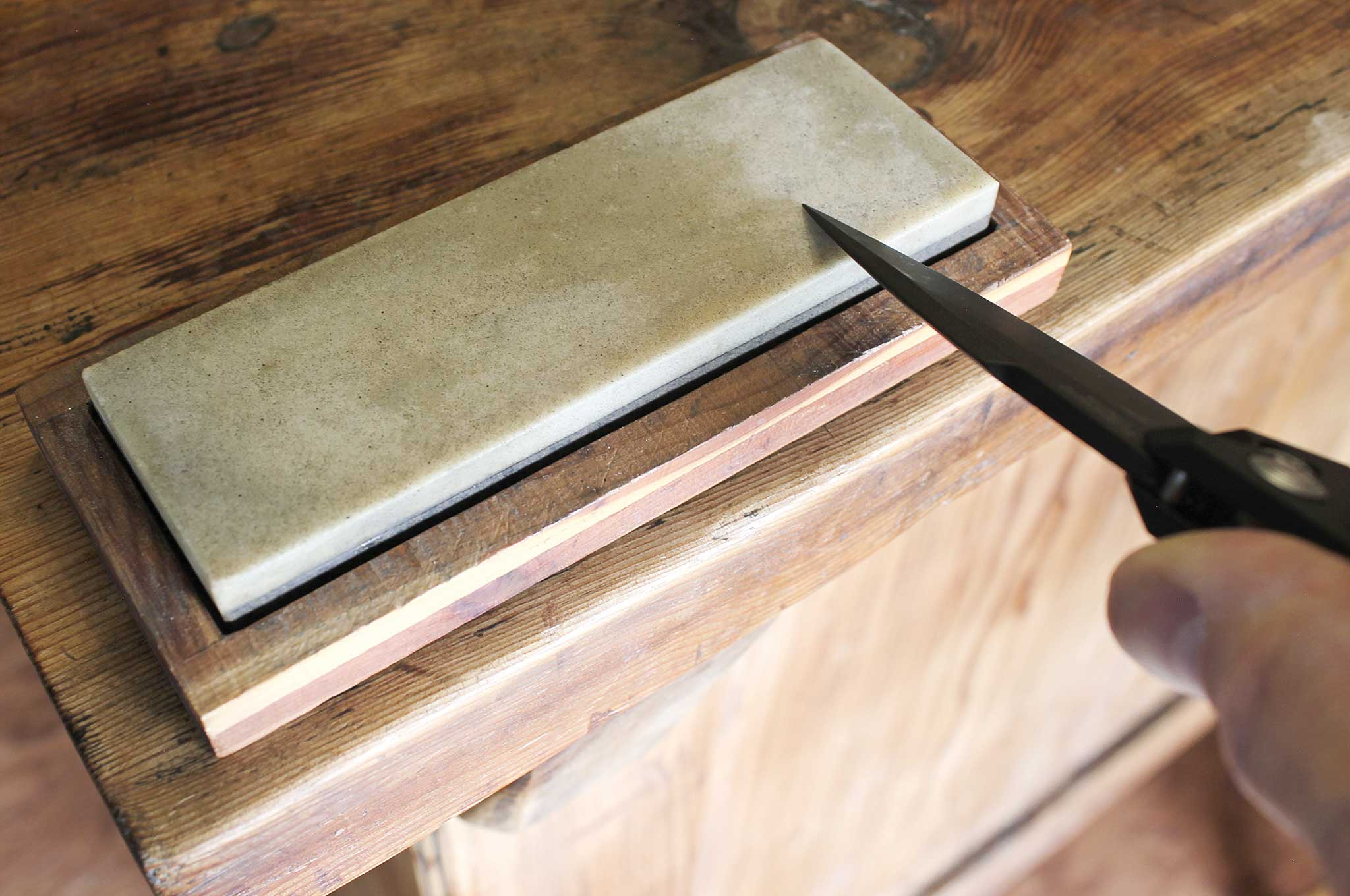 If you want to have any hope of sharpening a knife on an improvised abrasive, first learn how to do it with a traditional flat stone. After determining the proper angle, start with the heel of the edge closest to the handle and draw the entire edge across the stone as if trying to slice off a thin layer. Repeat on the other side and keep going until you've achieved the desired degree of sharpness.