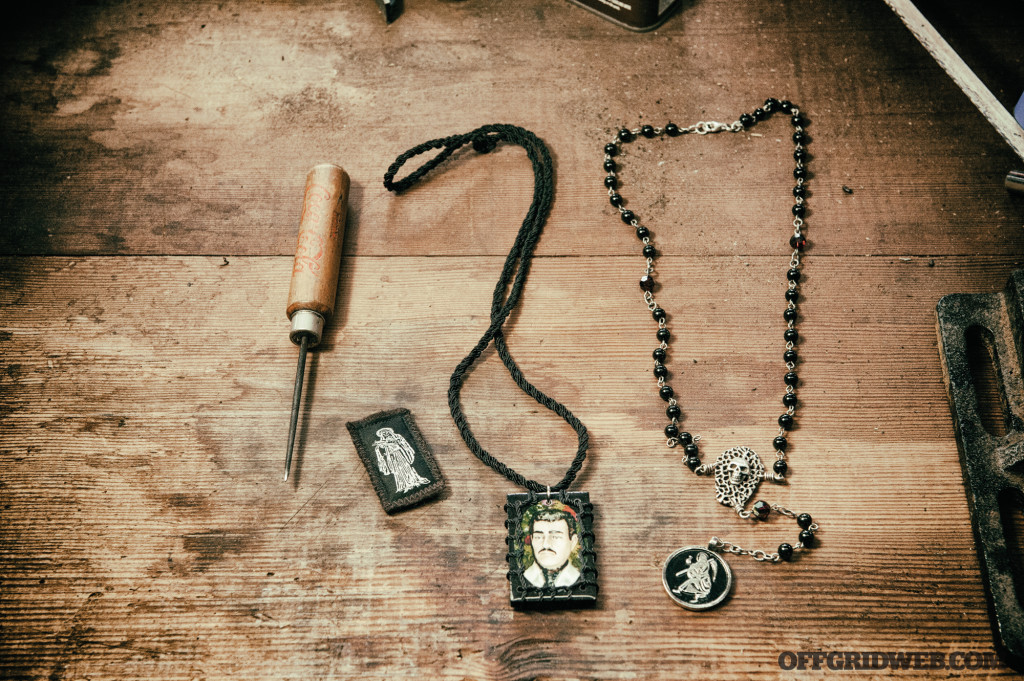 A small assortment of Mexican criminal occult iconography, and icepick death threat, Malverde necklace and Santa Muerte rosarie.
